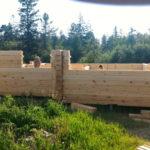 стройка дома из прямоугольного деревянного бруса на фундаменте из винтовых свай